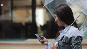 Όμορφη νέα επιχειρησιακή γυναίκα που χρησιμοποιεί το smartphone που περπατά στην οδό στο βροχερό καιρό, χαμόγελο, που κρατά την ο φιλμ μικρού μήκους
