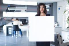 Όμορφη, νέα επιχειρησιακή κυρία στο μαύρο ισχυρό κενό έγγραφο λαβής ακολουθίας Στοκ Φωτογραφία