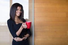 Όμορφη, νέα επιχειρησιακή κυρία στο μαύρο ισχυρό κόκκινο φλυτζάνι λαβής ακολουθίας Στοκ φωτογραφίες με δικαίωμα ελεύθερης χρήσης