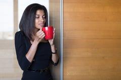 Όμορφη, νέα επιχειρησιακή κυρία στο μαύρο ισχυρό κόκκινο φλυτζάνι λαβής ακολουθίας Στοκ Εικόνα