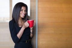 Όμορφη, νέα επιχειρησιακή κυρία στο μαύρο ισχυρό κόκκινο φλυτζάνι λαβής ακολουθίας Στοκ Εικόνες