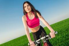 Όμορφη νέα λεπτή γυναίκα που οδηγά ένα ποδήλατο Στοκ Φωτογραφίες