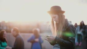 Όμορφη νέα Ευρωπαία γυναίκα στο μοντέρνο καπέλο που χρησιμοποιεί το smartphone app στη μουτζουρωμένη πολυάσχολη συσσωρευμένη οδό  απόθεμα βίντεο