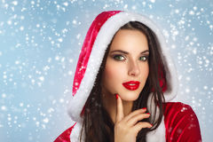 Όμορφη νέα ευτυχής γυναίκα στα ενδύματα Άγιου Βασίλη πέρα από το υπόβαθρο Χριστουγέννων ανασκόπηση πέρα από τη χαμογ& Πορτρέτο ομ Στοκ φωτογραφία με δικαίωμα ελεύθερης χρήσης