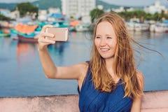 Όμορφη νέα εύθυμη γυναίκα που παίρνει ένα selfie στα πλαίσια της θάλασσας και των βιετναμέζικων βαρκών Στοκ Εικόνες