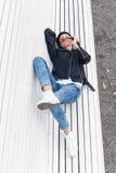 Όμορφη νέα θηλυκή συνεδρίαση σε έναν πάγκο πάρκων Στοκ Φωτογραφίες