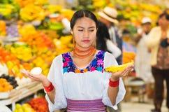 Όμορφη νέα ισπανική γυναίκα που φορά την των Άνδεων παραδοσιακή τοποθέτηση μπλουζών για την μπανάνα και το κρεμμύδι εκμετάλλευσης Στοκ εικόνες με δικαίωμα ελεύθερης χρήσης