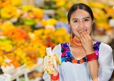 Όμορφη νέα ισπανική γυναίκα που φορά την των Άνδεων παραδοσιακή τοποθέτηση μπλουζών για τη κάμερα τρώγοντας την μπανάνα μέσα στα  Στοκ Εικόνες