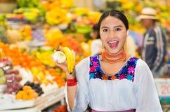 Όμορφη νέα ισπανική γυναίκα που φορά την των Άνδεων παραδοσιακή τοποθέτηση μπλουζών για την μπανάνα και το κρεμμύδι εκμετάλλευσης Στοκ εικόνα με δικαίωμα ελεύθερης χρήσης