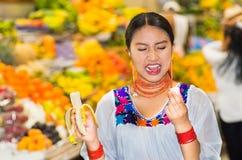 Όμορφη νέα ισπανική γυναίκα που φορά την των Άνδεων παραδοσιακή τοποθέτηση μπλουζών για τη κάμερα τρώγοντας την μπανάνα, που κάνε Στοκ Εικόνα