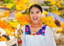 Όμορφη νέα ισπανική γυναίκα που φορά την των Άνδεων παραδοσιακή τοποθέτηση μπλουζών για τη κάμερα τρώγοντας την μπανάνα μέσα στα  Στοκ εικόνες με δικαίωμα ελεύθερης χρήσης