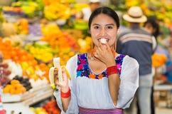 Όμορφη νέα ισπανική γυναίκα που φορά την των Άνδεων παραδοσιακή τοποθέτηση μπλουζών για τη κάμερα τρώγοντας την μπανάνα μέσα στα  Στοκ φωτογραφία με δικαίωμα ελεύθερης χρήσης