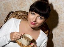 Όμορφη νέα καυκάσια γυναίκα που κρατά ένα φλυτζάνι του cappuccino Στοκ φωτογραφίες με δικαίωμα ελεύθερης χρήσης