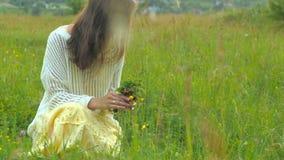 Όμορφη νέα καυκάσια γυναίκα που συλλέγει τα λουλούδια στον τομέα 4K απόθεμα βίντεο
