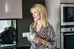 Όμορφη νέα καυκάσια γυναίκα στην κουζίνα με το τσάι φλυτζανιών στοκ φωτογραφία