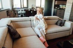 Όμορφη νέα καυκάσια γυναίκα στον καναπέ με το τσάι φλυτζανιών στοκ εικόνα με δικαίωμα ελεύθερης χρήσης