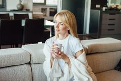 Όμορφη νέα καυκάσια γυναίκα στον καναπέ με το τσάι φλυτζανιών στοκ εικόνες