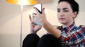 Όμορφη νέα καυκάσια συνεδρίαση γυναικών με τα ακουστικά γύρω από το λαιμό της που χρησιμοποιεί μια εφαρμογή σε ένα smartphone και φιλμ μικρού μήκους