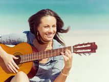 Όμορφη νέα κιθάρα παιχνιδιού γυναικών στην παραλία Στοκ εικόνα με δικαίωμα ελεύθερης χρήσης