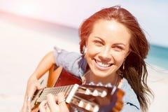 Όμορφη νέα κιθάρα παιχνιδιού γυναικών στην παραλία Στοκ εικόνες με δικαίωμα ελεύθερης χρήσης