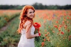 Όμορφη νέα κοκκινομάλλης γυναίκα στον τομέα παπαρουνών που κρατά μια ανθοδέσμη των παπαρουνών στοκ εικόνα