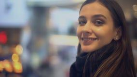 Όμορφη νέα κυρία που γυρίζει και που χαμογελά στη κάμερα, που στέκεται στο σιδηροδρομικό σταθμό απόθεμα βίντεο
