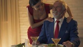 Όμορφη νέα κυρία που τρίβει τους ώμους στον παλαιό πλούσιο άνθρωπο, που φλερτάρει κατά την ημερομηνία απόθεμα βίντεο