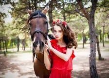 Όμορφη νέα κυρία που φορά το κόκκινο φόρεμα που οδηγά ένα άλογο στην ηλιόλουστη θερινή ημέρα Brunette με τη μακριά σγουρή τρίχα μ Στοκ Εικόνες