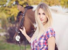 Όμορφη νέα κυρία που φορούν την μπλούζα και τζιν που οδηγούν ένα άλογο Στοκ φωτογραφία με δικαίωμα ελεύθερης χρήσης