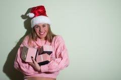 Όμορφη νέα κυρία στο καπέλο Santa που κρατά τρία Στοκ Εικόνα