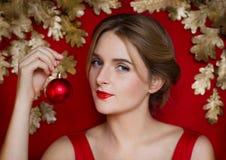 Όμορφη νέα κόκκινη χειλική πολυτελής Χαρούμενα Χριστούγεννα γυναικών σε ένα κόκκινο υπόβαθρο με το χρυσό Στοκ Εικόνα