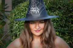 Όμορφη νέα μάγισσα με τα πράσινα μάτια και το καπέλο υπαίθρια Στοκ Φωτογραφίες