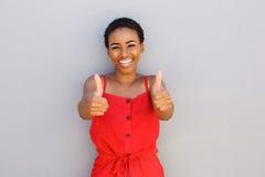 Όμορφη νέα μαύρη γυναίκα που χαμογελά με τους αντίχειρες επάνω στη χειρονομία χεριών Στοκ Φωτογραφίες