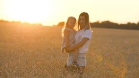 Όμορφη νέα μητέρα και η κόρη της που έχουν τη διασκέδαση στον τομέα σίτου