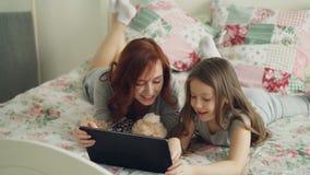 Όμορφη νέα μητέρα και η χαριτωμένη κόρη της στις πυτζάμες που γελούν και που κοιτάζουν στην ψηφιακή ταμπλέτα στο κρεβάτι απόθεμα βίντεο