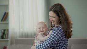 Όμορφη νέα μητέρα και χαριτωμένη κόρη μωρών που αγκαλιάζουν και που χαμογελούν, ευτυχές μέλλον απόθεμα βίντεο
