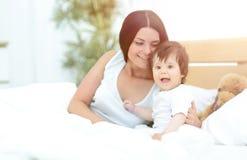 Όμορφη νέα μητέρα με ένα μωρό που βρίσκεται στο κρεβάτι και το χαμόγελο στοκ εικόνες