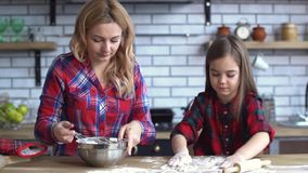 Όμορφη νέα μητέρα με την ξανθή μακρυμάλλη μίξη στο πιάτο και μικρό χαριτωμένο άτακτο παιχνίδι κοριτσιών με το αλεύρι στην κουζίνα απόθεμα βίντεο