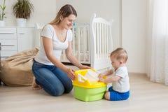 Όμορφη νέα μητέρα που διδάσκει το γιο 10 μηνών της που χρησιμοποιεί το δοχείο μωρών Στοκ Φωτογραφίες