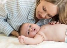Όμορφη νέα μητέρα που εξετάζει το γιο και το χαμόγελο μωρών της, που βρίσκονται στο κρεβάτι στο σπίτι Στοκ φωτογραφίες με δικαίωμα ελεύθερης χρήσης