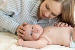 Όμορφη νέα μητέρα που εξετάζει το γιο και το χαμόγελο μωρών της, που βρίσκονται στο κρεβάτι στο σπίτι Στοκ φωτογραφία με δικαίωμα ελεύθερης χρήσης