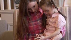 Όμορφη νέα μητέρα που κρατά την λίγη κόρη στα όπλα της απόθεμα βίντεο