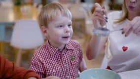 Όμορφη νέα μητέρα σε έναν καφέ Μια γυναίκα ταΐζει το γιο της με τα ζυμαρικά, δίπλα στην κόρη της τρώει το πιάτο της απόθεμα βίντεο
