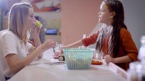 Όμορφη νέα μητέρα σε έναν καφέ Τα παιδιά στην περιοχή παιχνιδιού, η γυναίκα προσέχουν τους και τα ποτά απόθεμα βίντεο