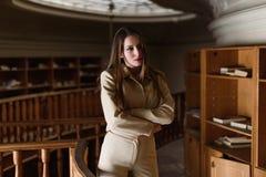 Όμορφη νέα μοντέρνη γυναικεία τοποθέτηση στην εκλεκτής ποιότητας βιβλιοθήκη Στοκ Φωτογραφίες