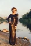 Όμορφη νέα μοντέρνη τοποθέτηση γυναικών στο φόρεμα στην ακτή ποταμών Στοκ εικόνα με δικαίωμα ελεύθερης χρήσης