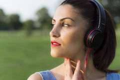 Όμορφη νέα μουσική ακούσματος γυναικών μέσω των ακουστικών Στοκ φωτογραφίες με δικαίωμα ελεύθερης χρήσης