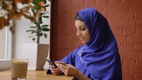 Όμορφη νέα μουσουλμανική γυναίκα στο μπλε hijab που ξαναγράφει τις πληροφορίες από την κάρτα στο τηλέφωνό της, που κάθεται στο σύ απόθεμα βίντεο