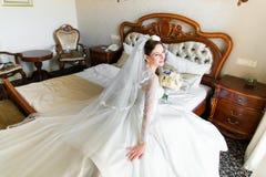 Όμορφη νέα νύφη με το makeup, τη φαντασία hairstyle στο άσπρο φόρεμα και τη συνεδρίαση πέπλων στο κρεβάτι Στοκ εικόνες με δικαίωμα ελεύθερης χρήσης