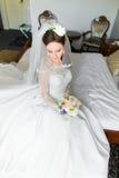 Όμορφη νέα νύφη με το makeup, τη φαντασία hairstyle στο άσπρο φόρεμα και τη συνεδρίαση πέπλων στο κρεβάτι που κοιτάζει κάτω Στοκ Φωτογραφίες